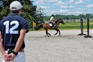 """Anna on approach under Daniel Stewart's eye during the """"playground"""" exercise at the July 2013 clinic.  My """"pressure"""" would have increased exponentially if these jumps had been about five holes higher.... Photo Credit Lauren Atherton Eventing"""