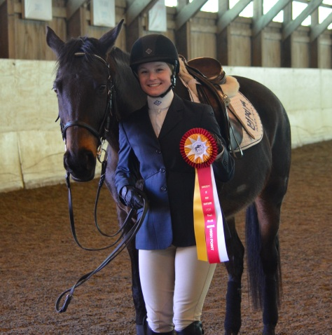A rider from Colby Sawyer's IHSA team poses after riding Lee to win reserve high point rider.