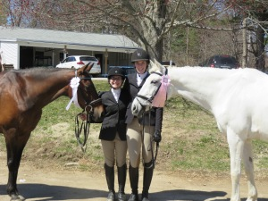Two UNH riders with leased horse Wiggle and UNH's Whisper celebrate after their first ever two phase competition.