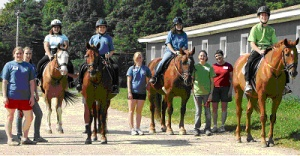 Participants in UNH's therapeutic riding program.  Shazaam, Marcy and Quill are all now retired, while Snowy (second from right) is a boarder who still works part time in the therapeutic program.